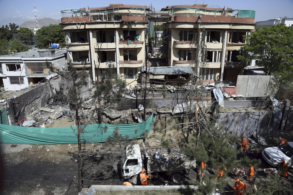 Afghan municipality workers clean a road in front of the damaged buildings, a day after an attack in Kabul, Afghanistan, Thursday, May 9, 2019.