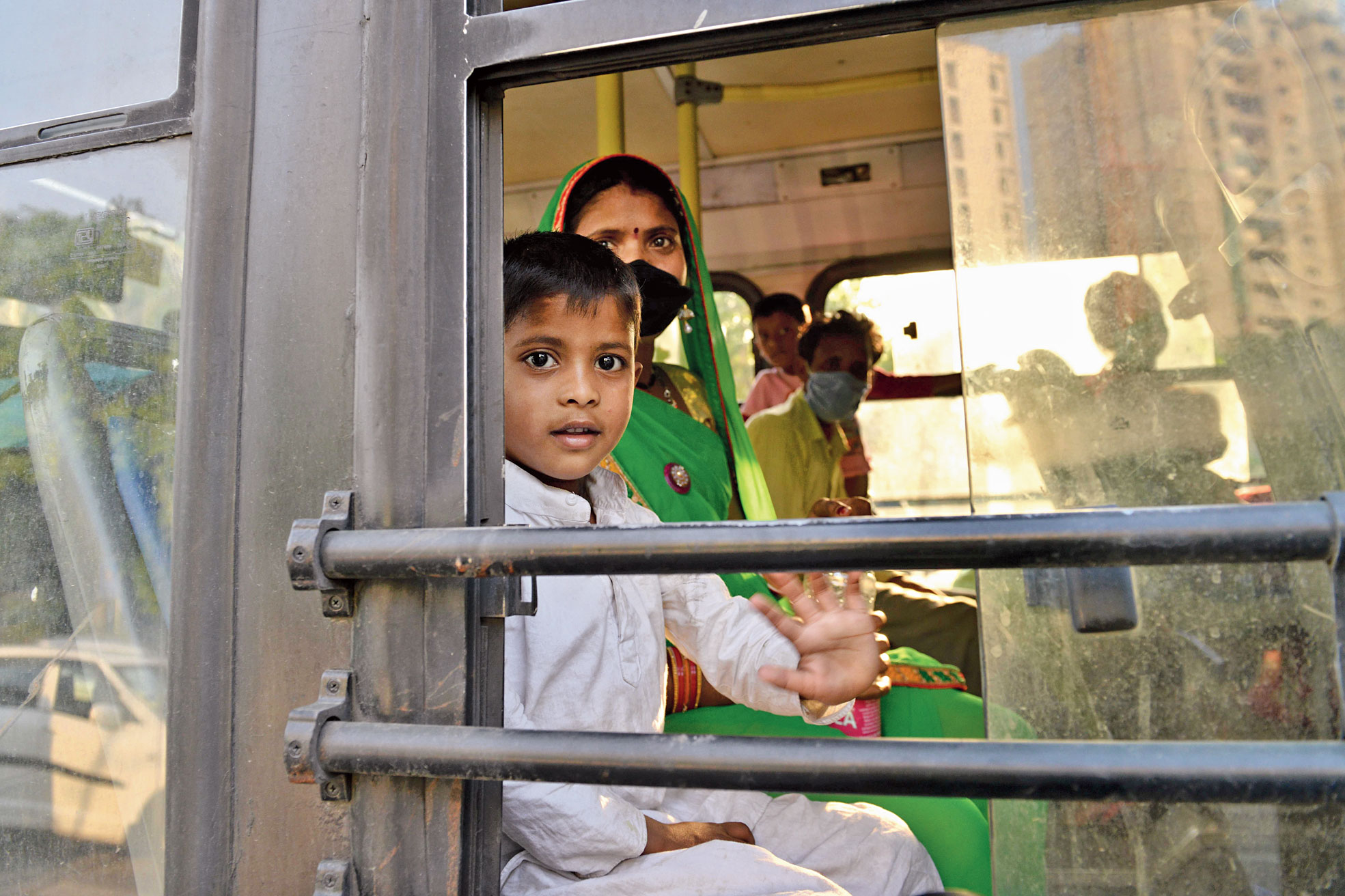 Migrant workers and their relatives sit in a bus at New Delhi railway station on Thursday before boarding a special train bound for their home states.