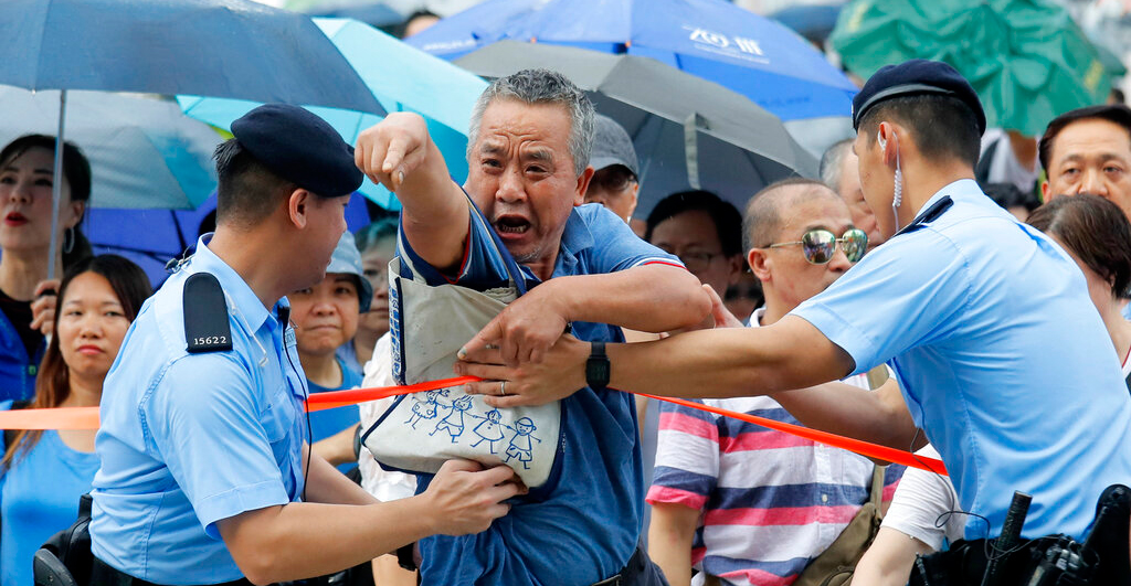 A pro-China's supporter shouts at pro-democracy protesters during a rally outside Legislative Council Complex in Hong Kong, Sunday, June 30, 2019.