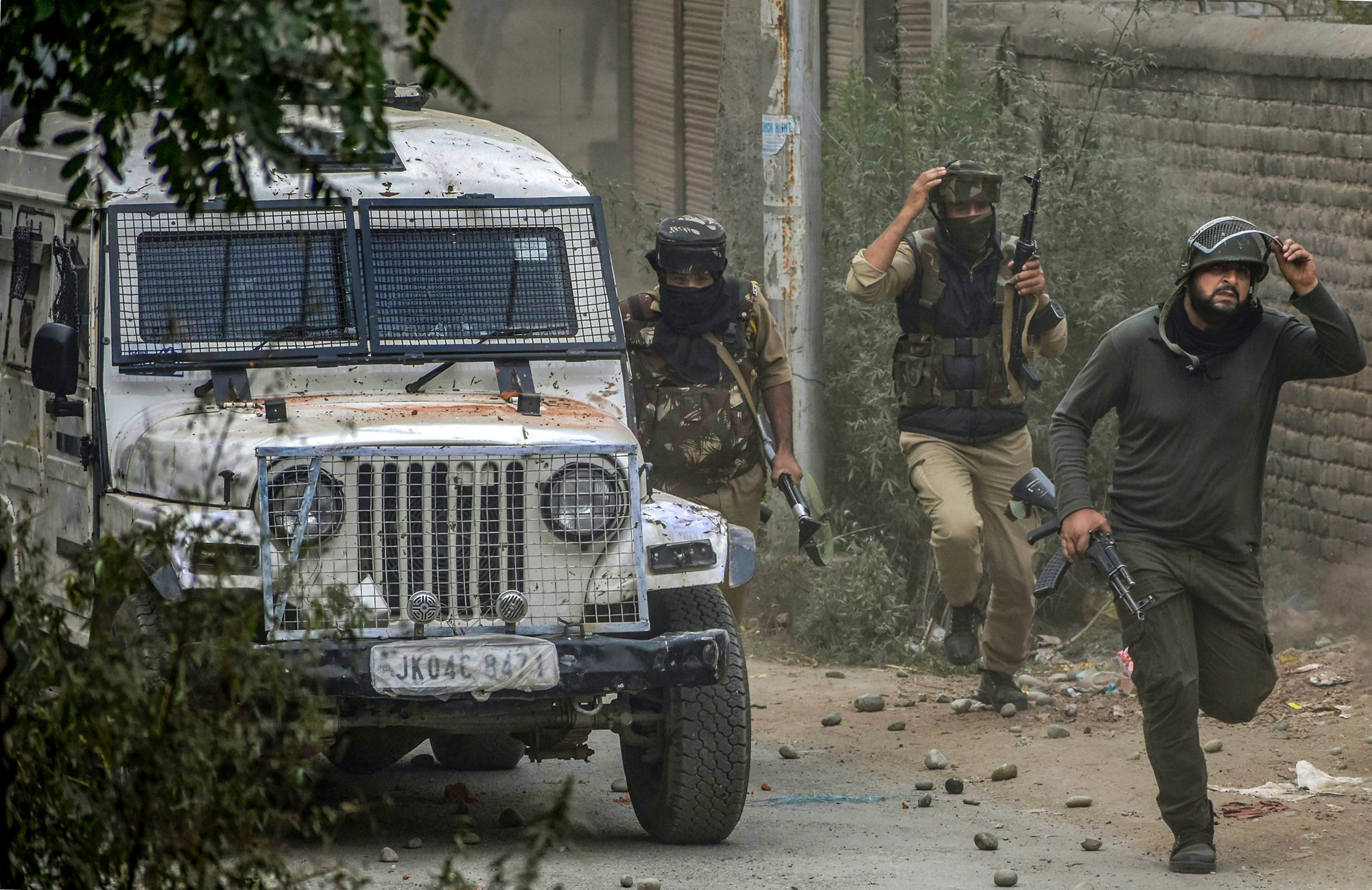 Special Operation Group of Jammu & Kashmir Police run towards the mosque where militants were hiding during an encounter at Panzan Chadoora area of Budgam district near Srinagar, on Thursday.