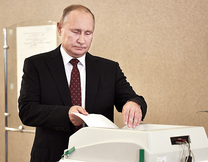 Russian President Vladimir Putin casts his ballot at a polling station during a city council election in Moscow on Sunday