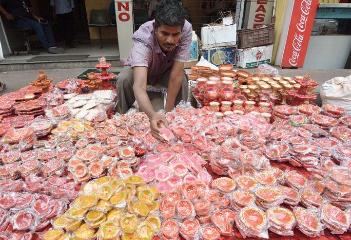 A vendor sells coloured earthen lamps in Guwahati on Thursday ahead of Diwali