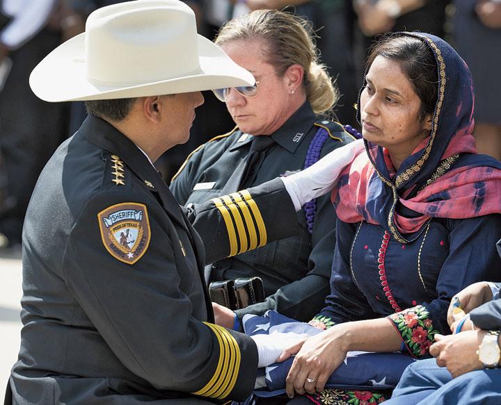Sheriff Ed Gonzalez presents deputy Sandeep Dhaliwal's widow, Harwinder Kaur Dhaliwal, with an American flag at Dhaliwal's funeral in Houston.
