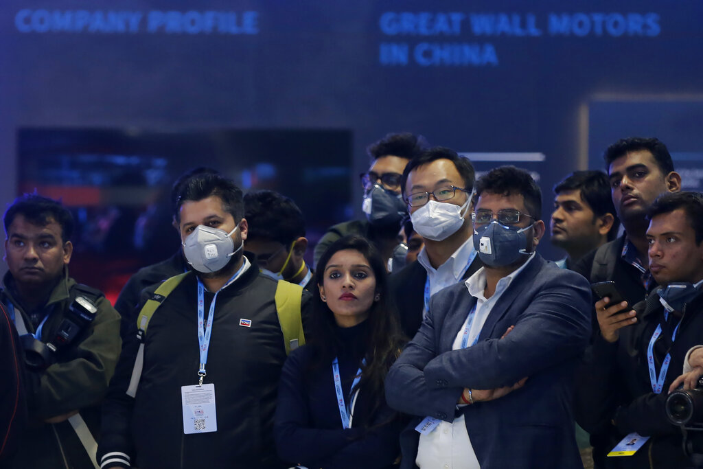 Delegates wear face mask as they attend an event at the Auto Expo in Greater Noida, near New Delhi, on Wednesday