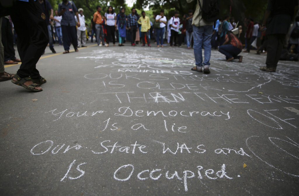 Activists draw murals and messages on a street during a protest against Indian government revoking Kashmir's special constitutional status in New Delhi, on Wednesday, Aug. 7, 2019.
