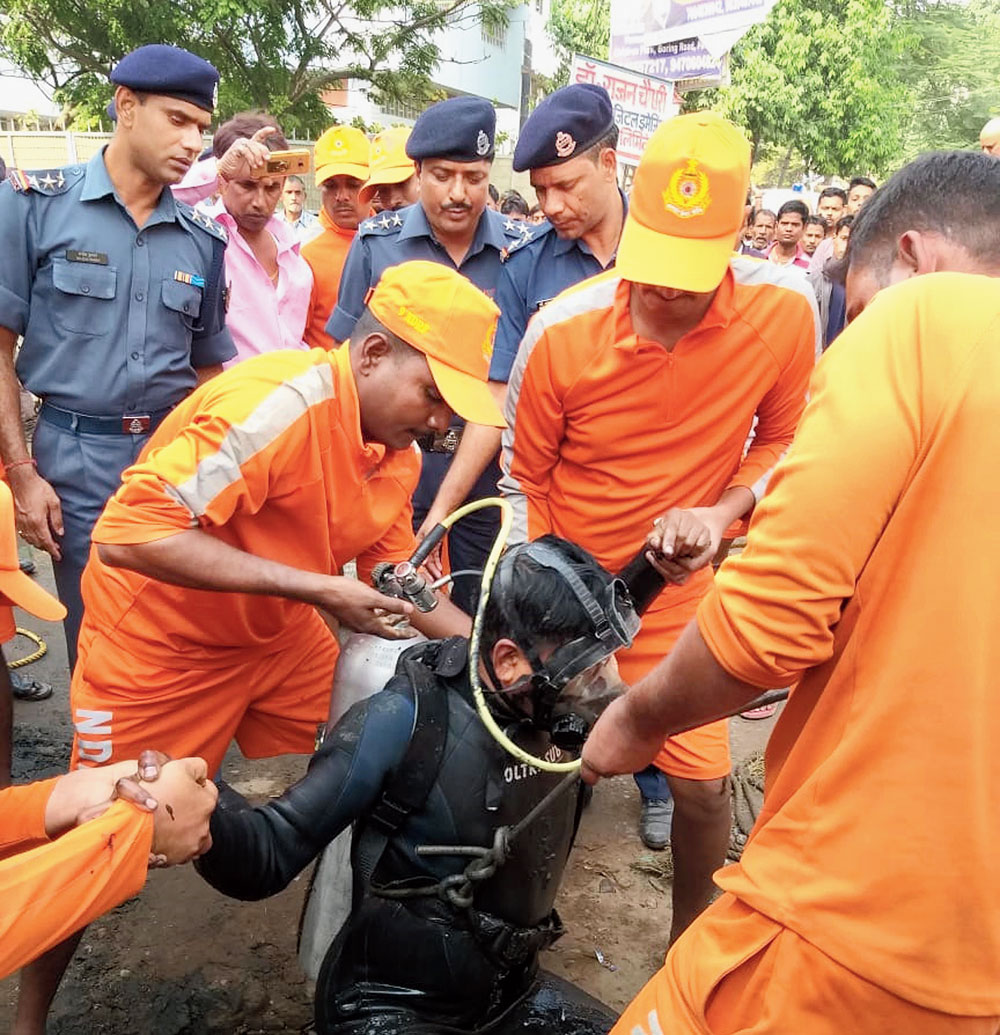 An NDRF diver emerges from a manhole during the search for 10-year-old Dipak Kumar on Tuesday