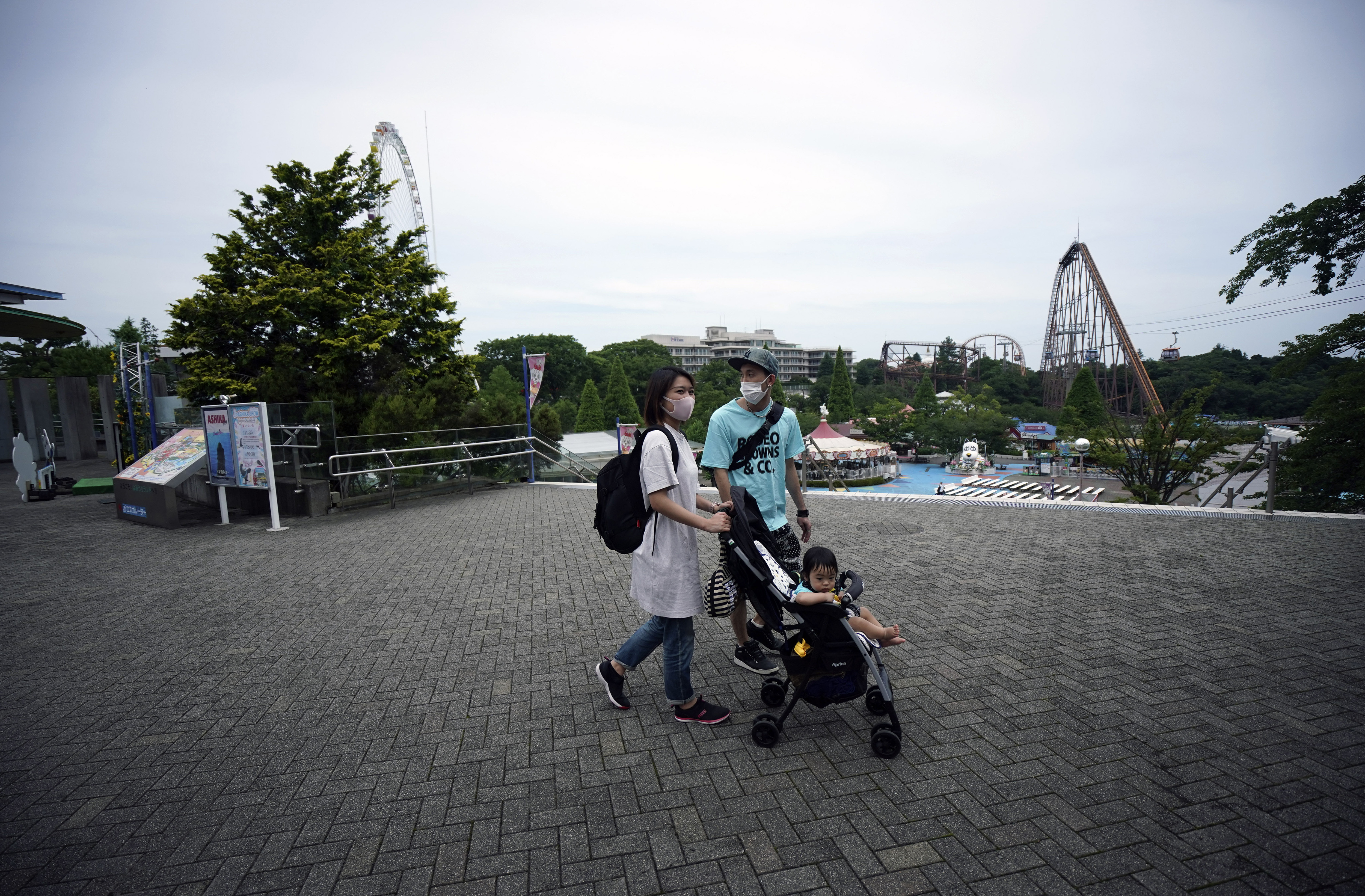 A family walks at the recently reopened Yomiuriland amusement park in Tokyo