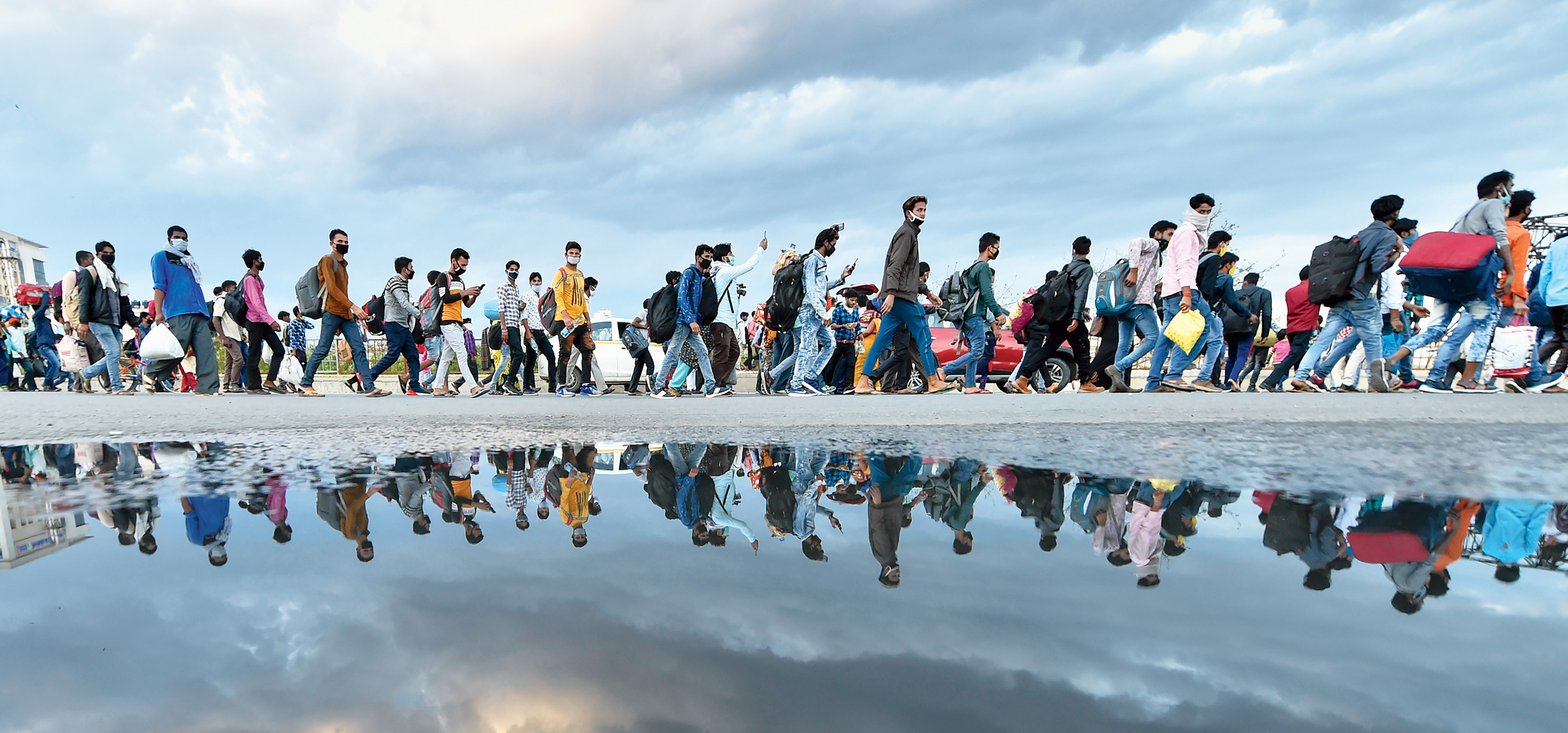 A group of migrant workers walk to their native places amid the nationwide complete lockdown, on the NH24 near Delhi-UP border in New Delhi, Friday, March 27, 2020