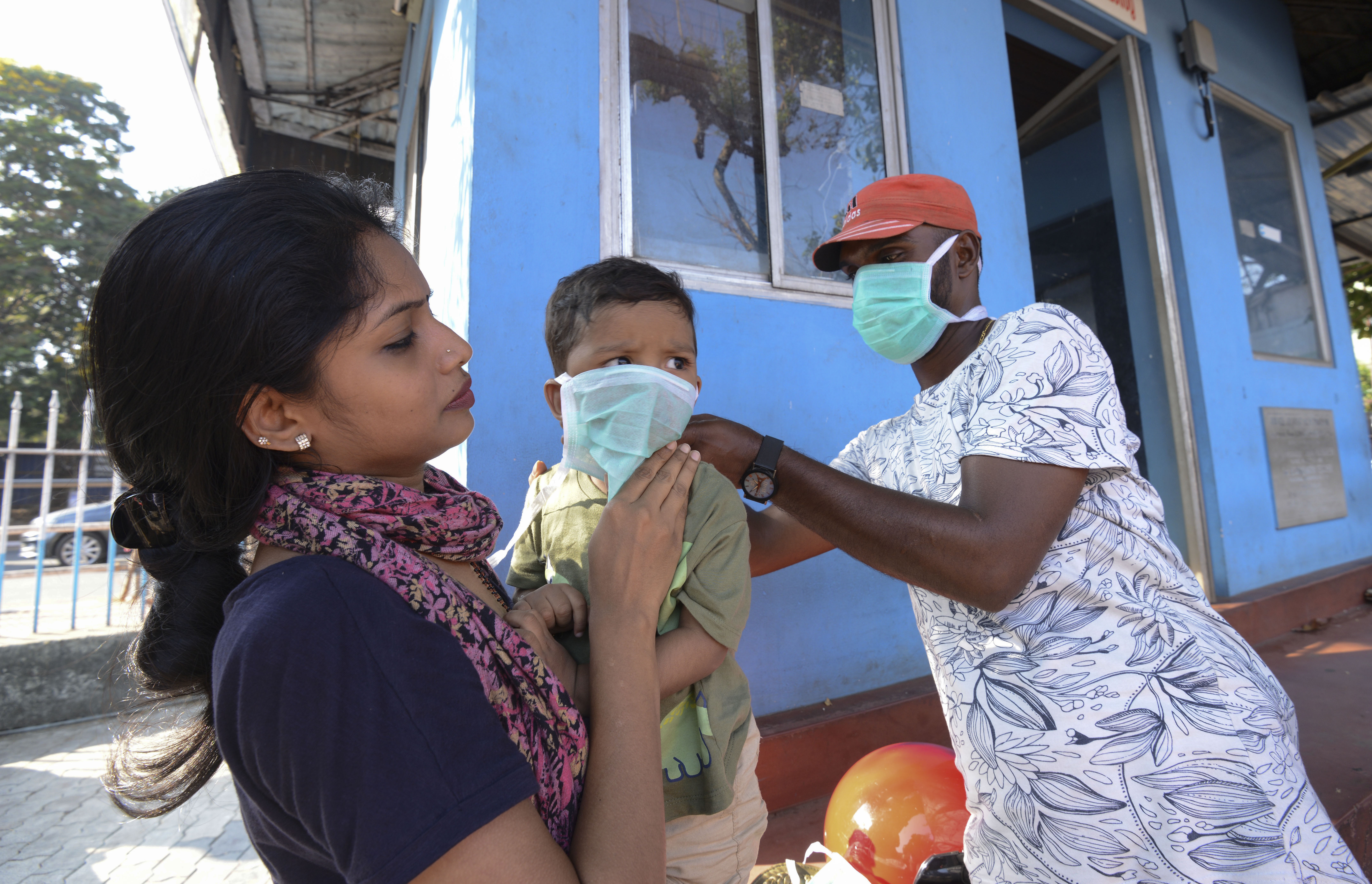 A man wearing a surgical mask makes a child wear one outside the government general hospital where a student who had been in Wuhan is kept in isolation in Thrissur, Kerala, India.
