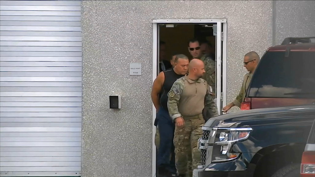 This frame grab from video provided by WPLG-TV shows FBI agents escorting Cesar Sayoc, in sleeveless shirt, in Miramar, Florida, on Friday.
