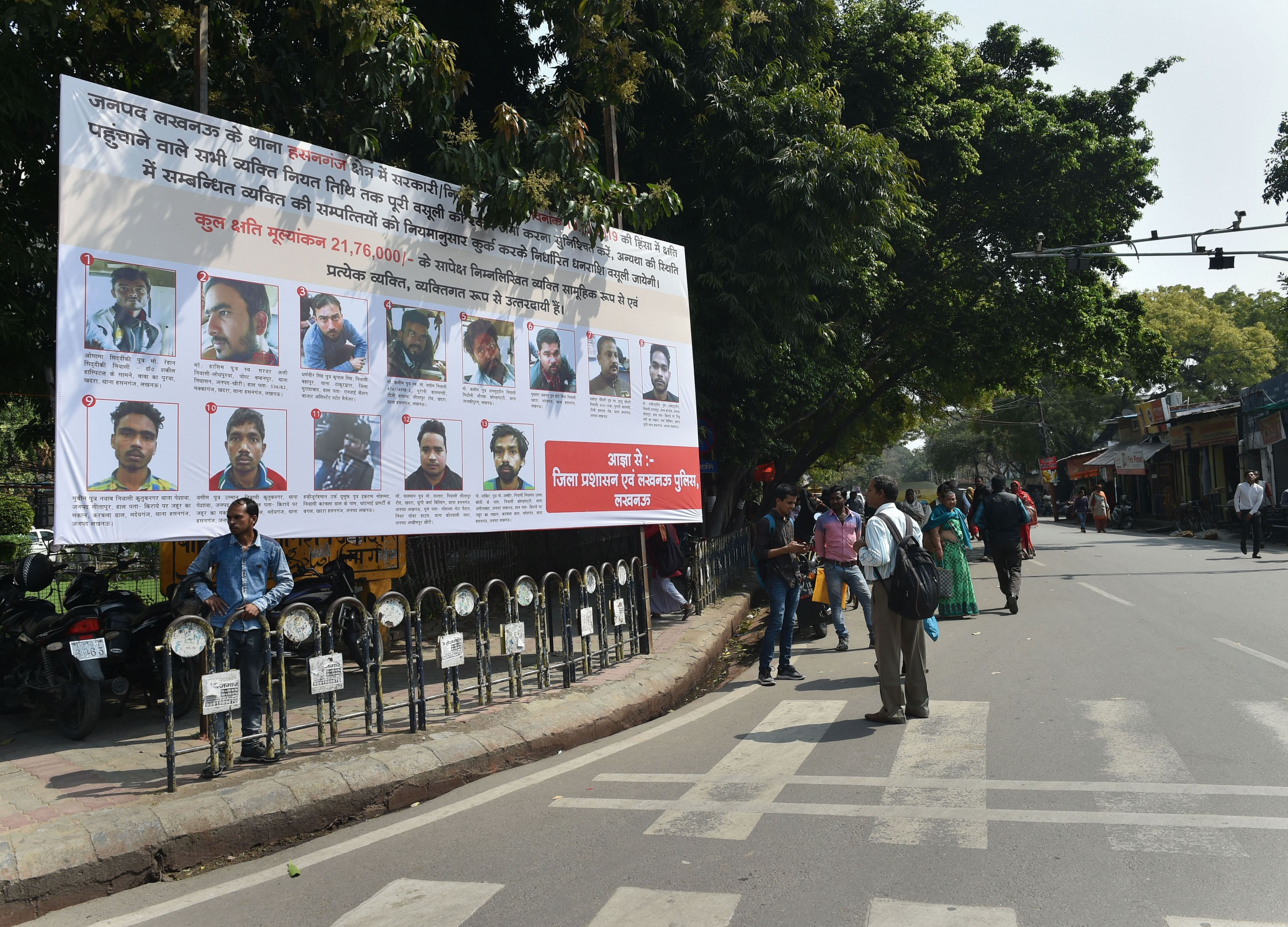 People walk past a poster displaying photographs of those who have been identified to pay the compensation for vandalizing public properties during protests against CAA, in Lucknow, Friday, March 6, 2020