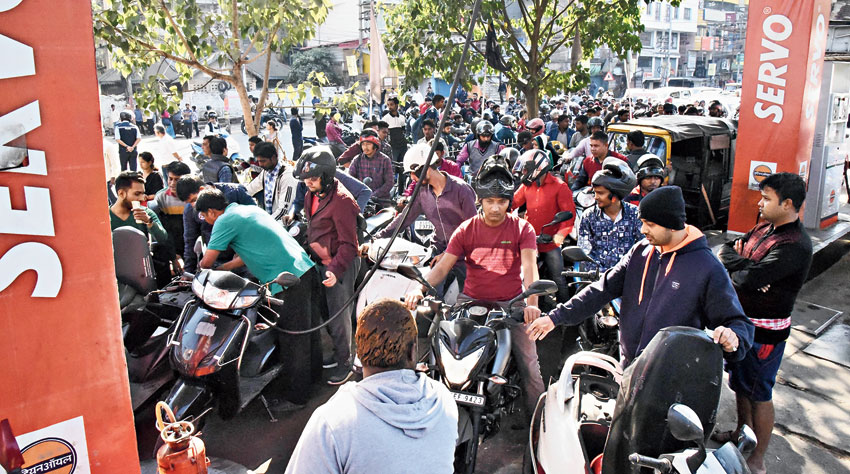 People queue up outside a petrol pump after curfew was relaxed in Guwahati on Friday