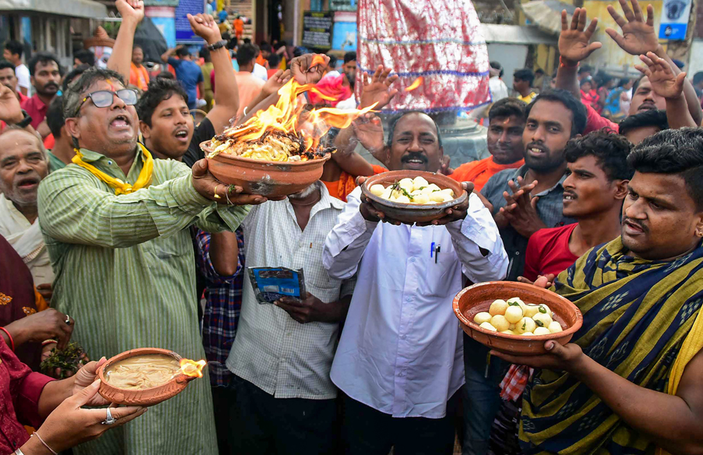 Members of Jagannath Sena offer Odisha 'rasagolla' to Lord Jagannath while performing 'deepadaan' in front of the Jagannath Temple  after the sweet got the GI tag, in Puri, Monday, July 29, 2019.