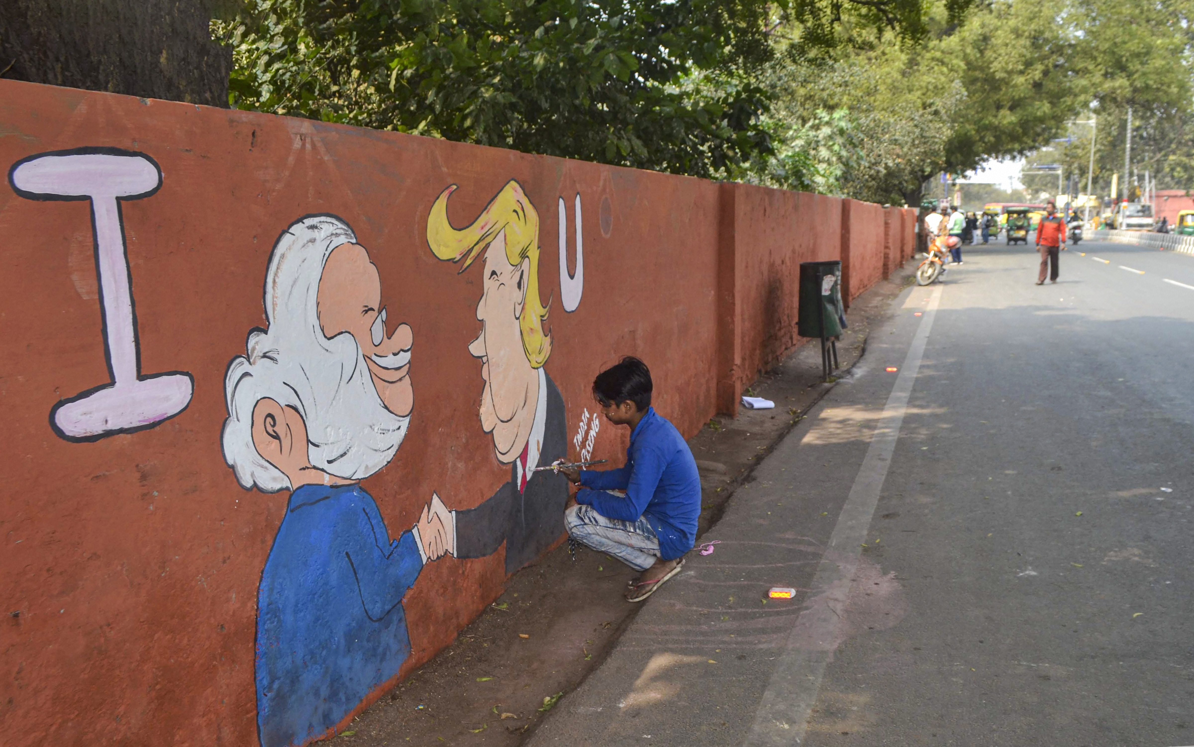 A worker paints on a wall on the route in which US President Donald Trump is scheduled to travel during his maiden visit to India, in Agra, Friday, February 21, 2020