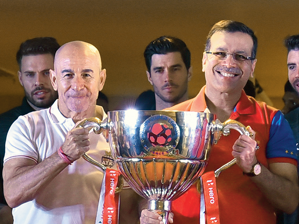 ATK head coach Antonio Lopez Habas and Sanjiv Goenka strike a pose with the ISL 2020 trophy at the RPSG House in Alipore on Sunday