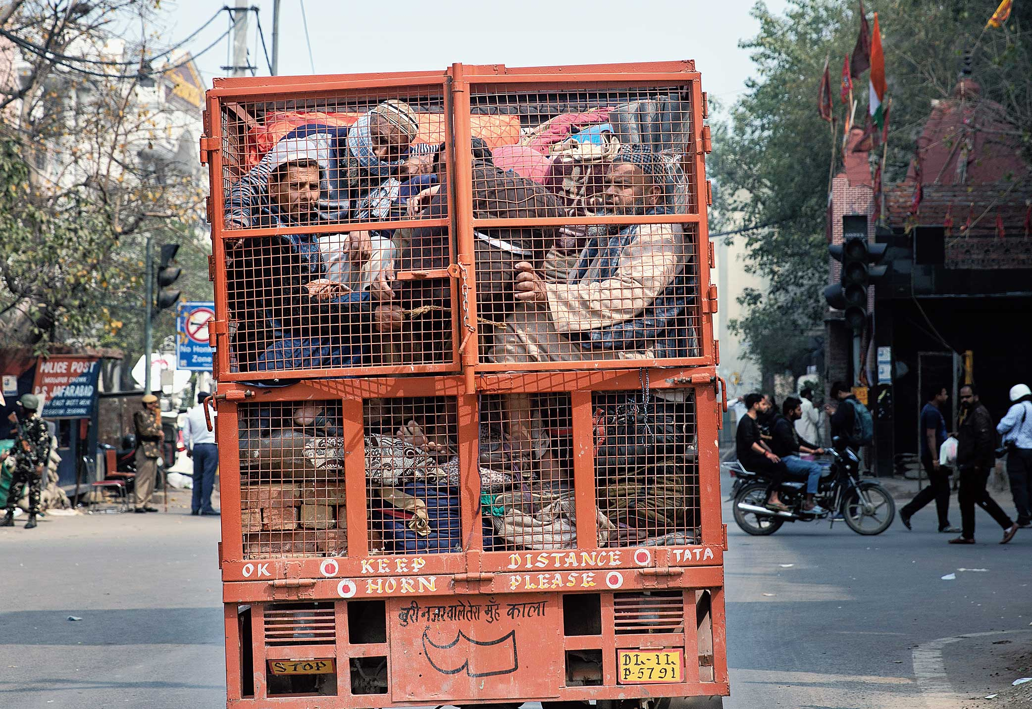 A group of Muslims huddle in the back of a mini-truck and leave the area after Tuesday's violence in New Delhi on Wednesday.