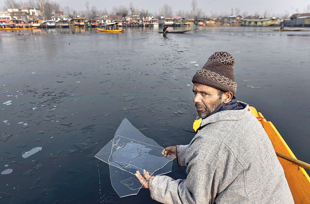 A boatman holds ice sheets from the partially frozen Dal Lake in Srinagar on Monday.