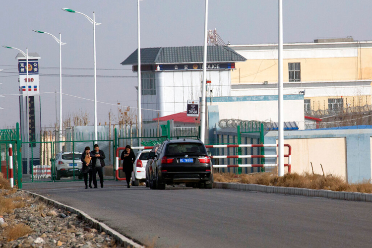 People walk past a police station by the Artux City Vocational Skills Education Training Service Center in Artux in China's Xinjiang