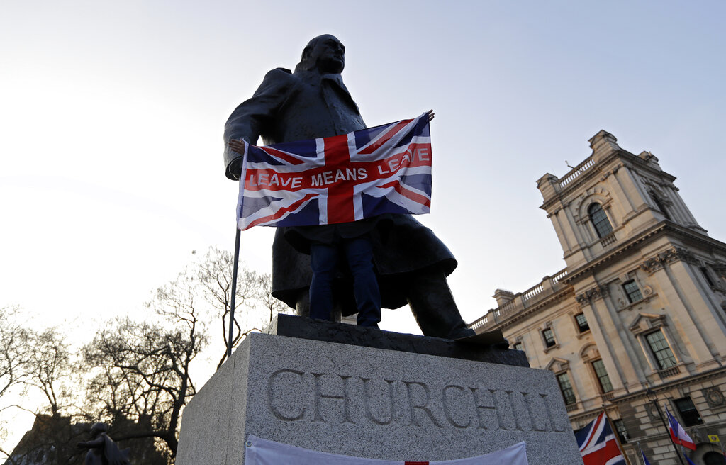 A man holds the British flag in front of the Winston Churchill statue in Westminster, London. Both Conservative and Labour members of Parliament keep voting down one plan after another, looking for the perfect fix, the pain-free exit from the EU. But there is none, because you can't fix stupid.