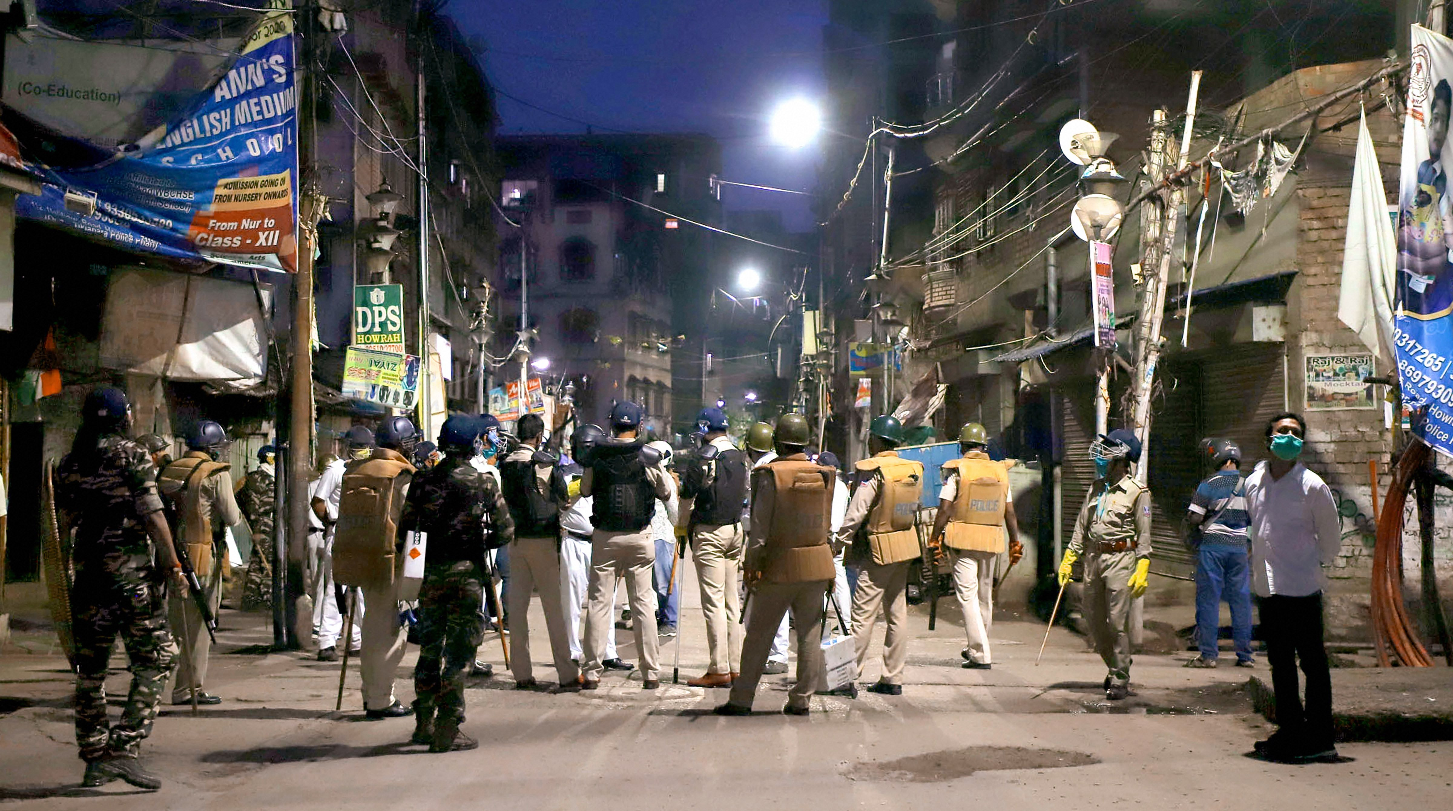 Police personnel stand guard after a mob attacked several policemen who were enforcing lockdown to prevent the spread of coronavirus at Tikiapara in Howrah district