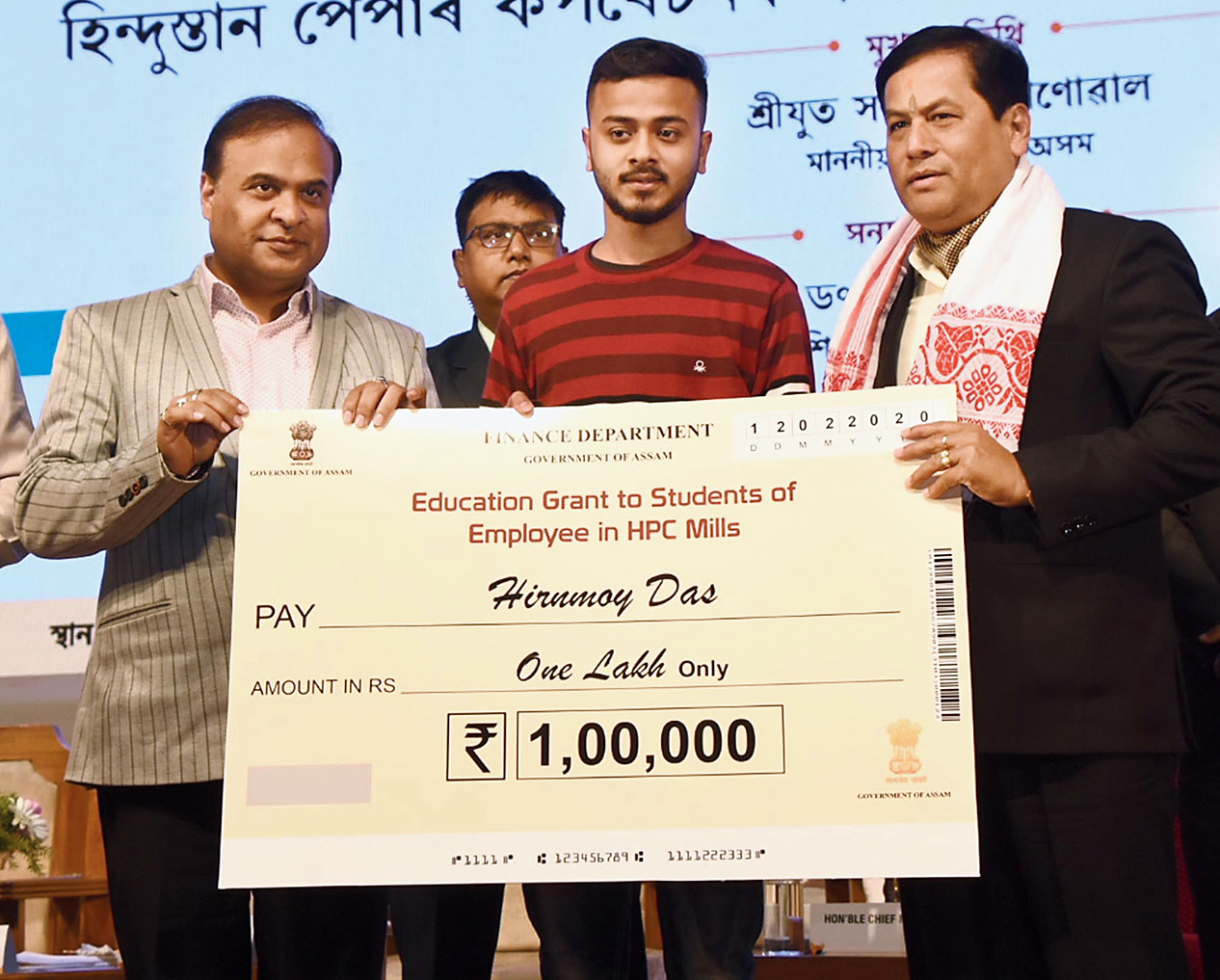 Himanta Biswa Sarma and Sarbananda Sonowal present a cheque to a student of a paper mill employee in Guwahati on Wednesday