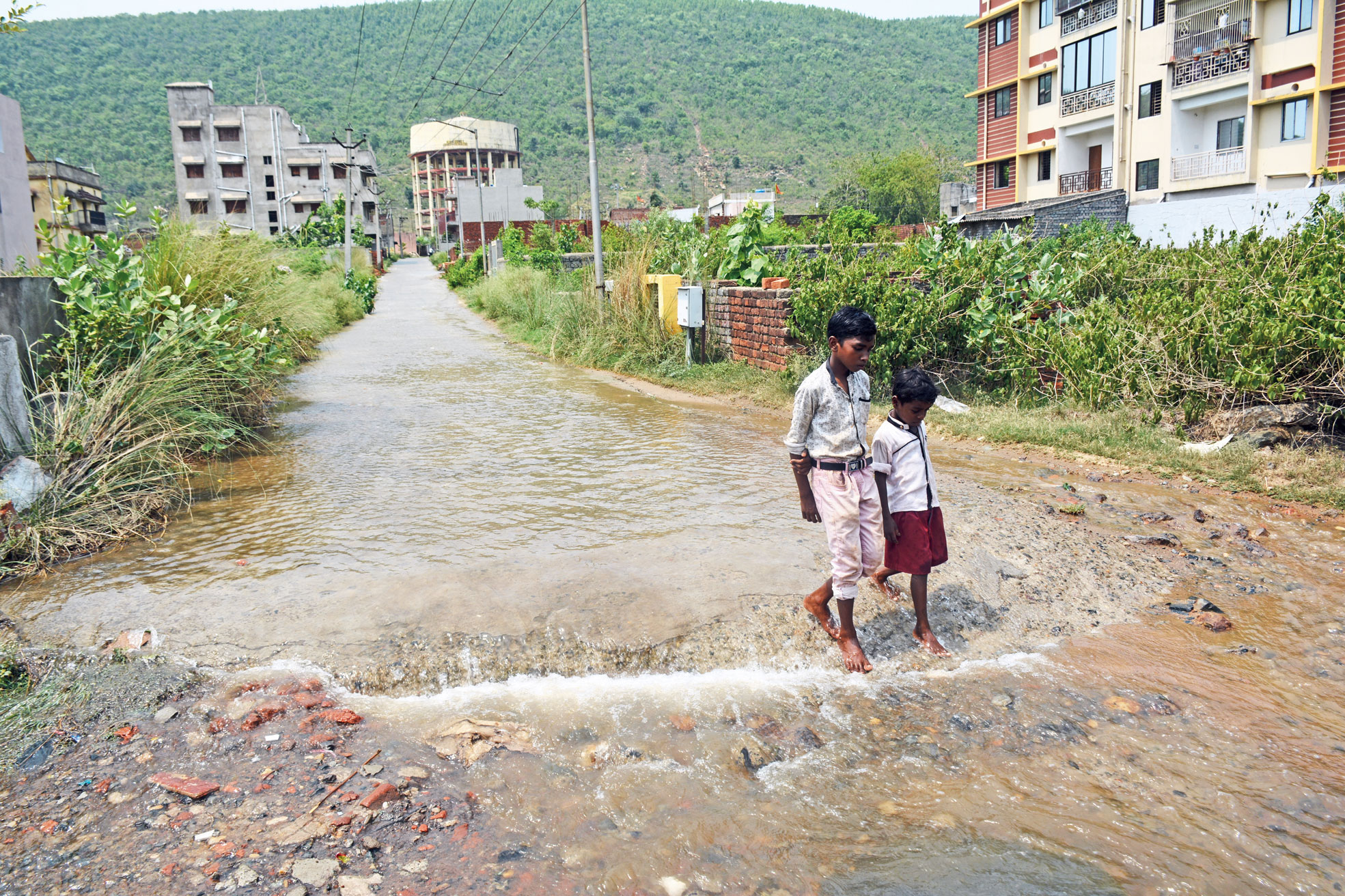 Kids wade through ankle-deep potable water at Nilgiri Colony in Mango, Jamshedpur, on Thursday.
