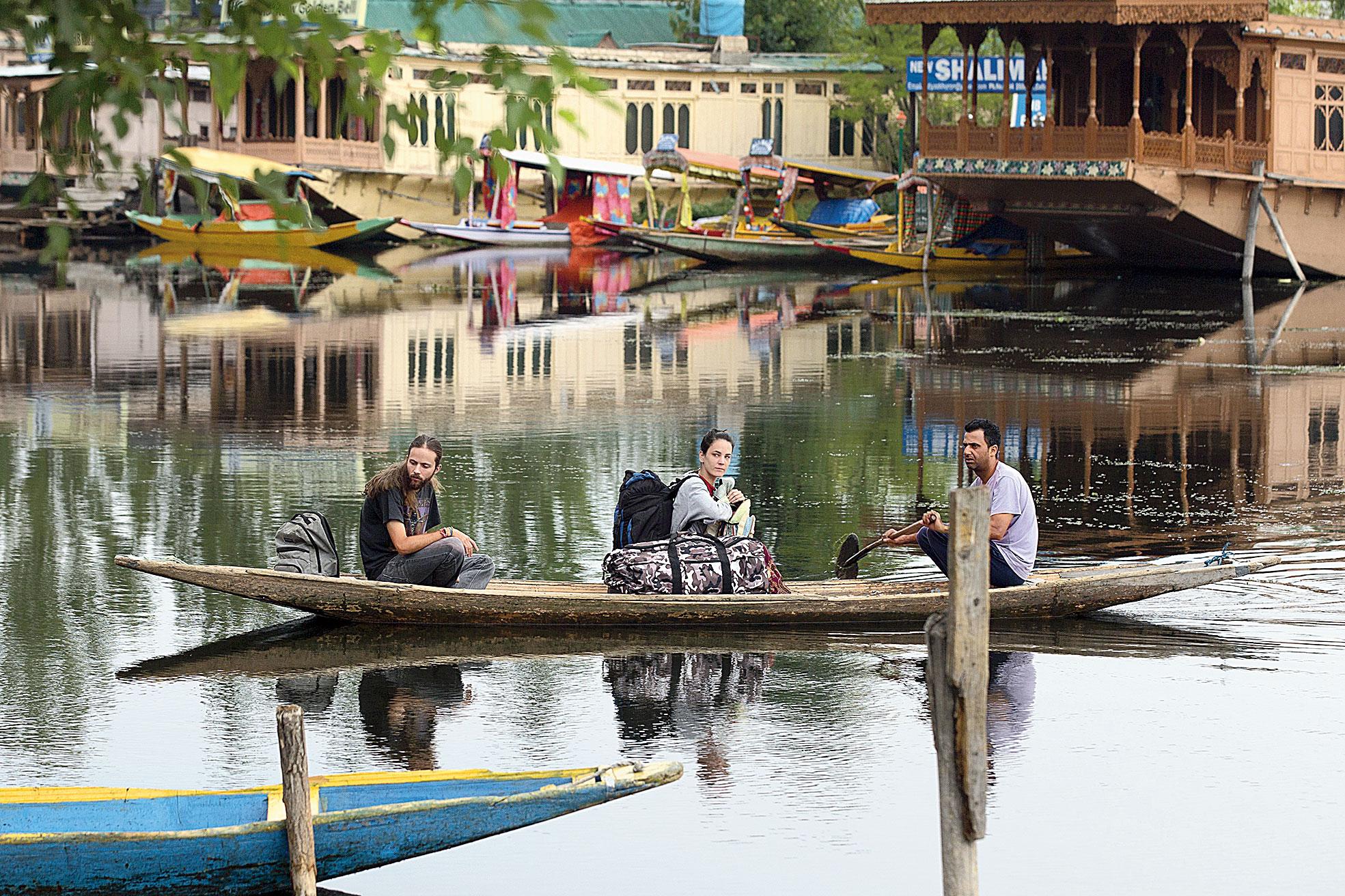 Tourists cross the Dal Lake on a shikara as they prepare to leave Srinagar on Saturday.